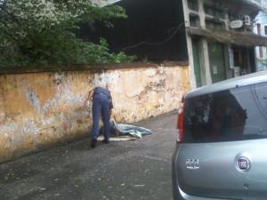 Guarda (com luvas) pedindo para morador acordar, explicando que não pode ficar ali deitado.